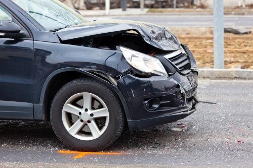 Blaues Auto mit schweren Schäden an der Front steht auf einer Straße.