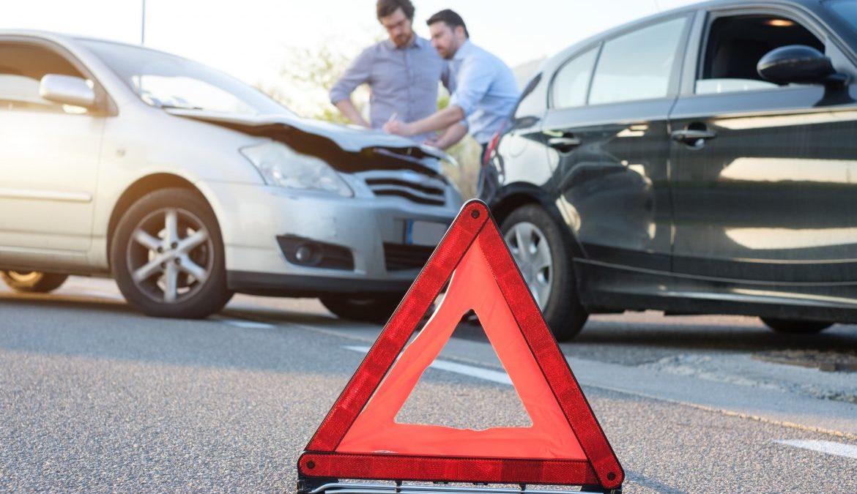 Warndreieck steht auf der Straße vor einem Unfall mit 2 Autos und 2 Männern im Hintergrund