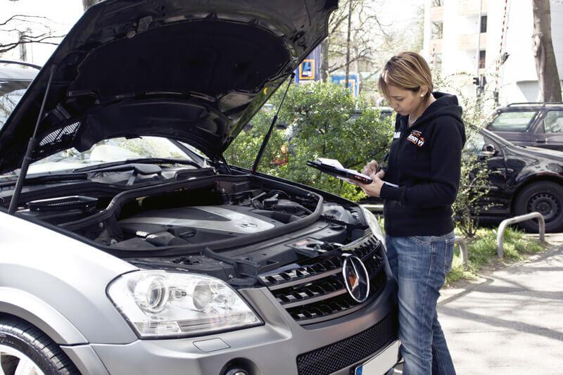 Gutachterin kontrolliert den Motor eines metallenen Mercedes