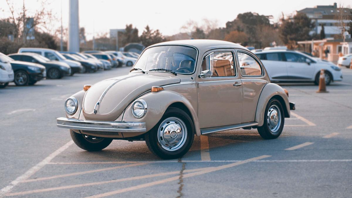 Besche VW Ente steht zwischen vielen Autos.