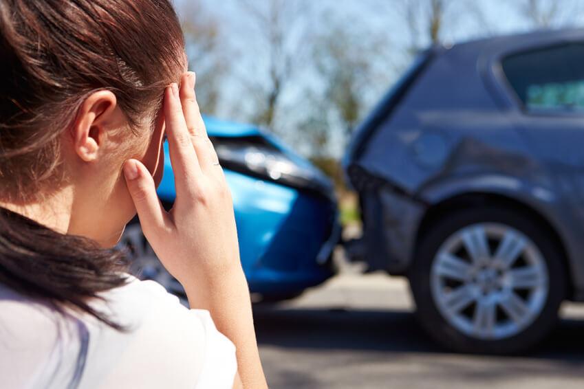 Vor 2 Autos die einen Unfall hatten steht eine Frau die sich Sorgen macht.
