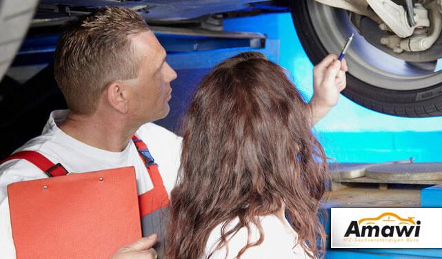 Kfz-Gutachter begutachtet mit einer Kunden die Reifen eines Autos.