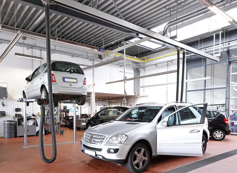 Mehrere Autos stehen in einer Autowerkstatt.