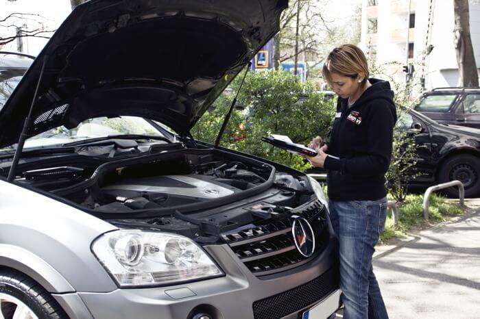 Kfz-Gutachterin Rudaina Amawi begutachtet den Motor eines Mercedes.