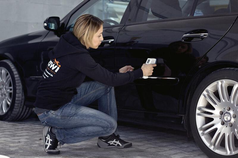 Kfz-Gutachterin begutachtet die Schäden an einem schwarzen Auto.