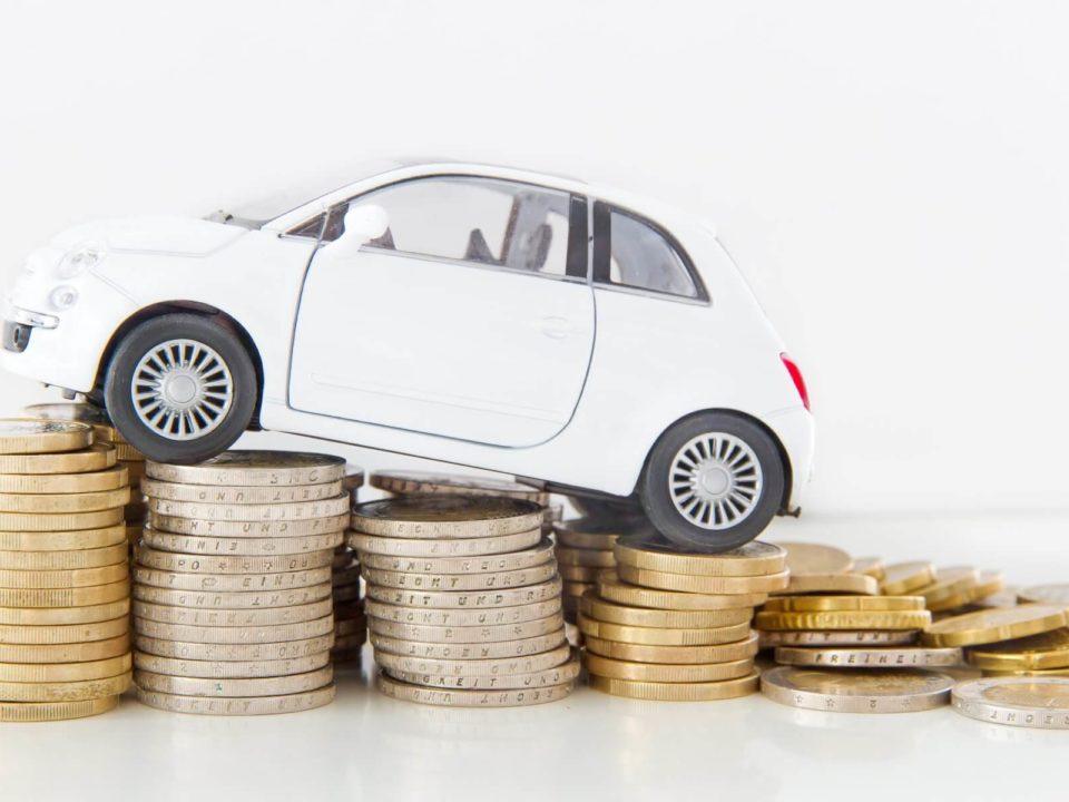 Ein kleines, weisses Auto fährt über einen Münzstapel.