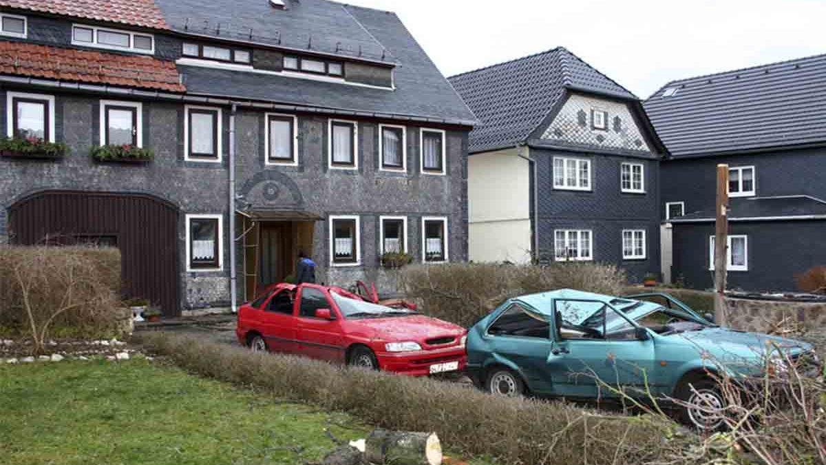 Zwei durch einen Sturm zerstörte Autos stehen in einem Hinterhof.