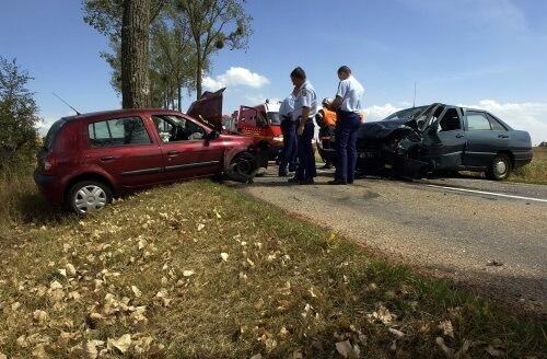 Mehrere Polizisten stehen an einem Unfallort mit 2 kaputten Autos.
