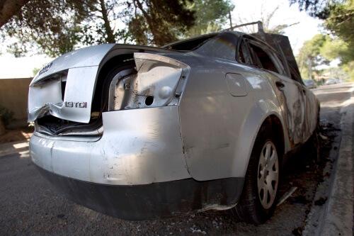 Stark zerstörtes, metallenes Auto steht auf einer Straße.