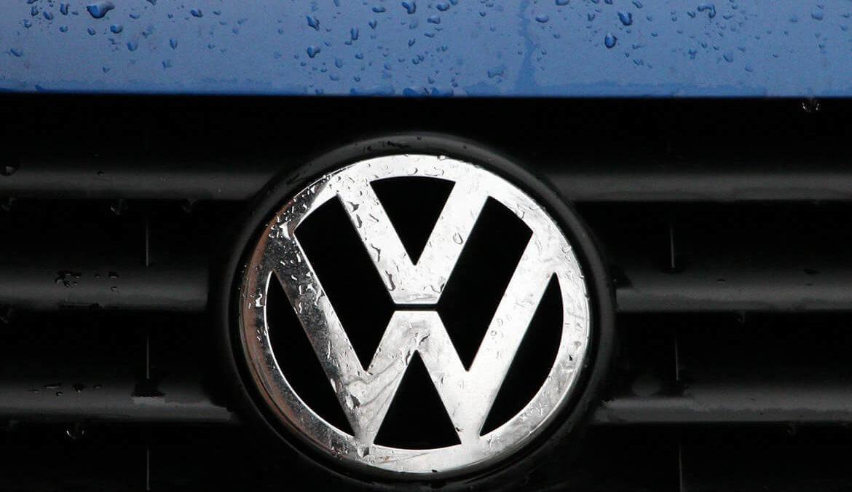 Nahaufnahme eines VW-Zeichens an einem Auto.