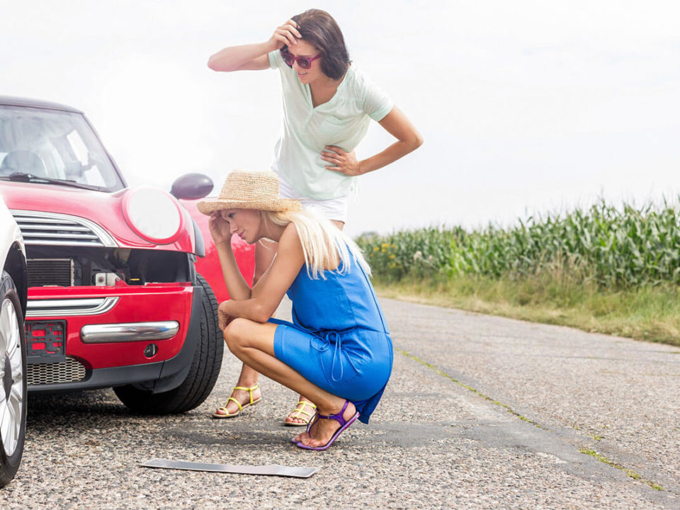 2 Frauen gucken sich den Schaden bei einem Autounfall an.