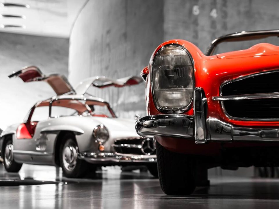 Ein roter und ein weisser Oldtimer stehen in einer Halle.