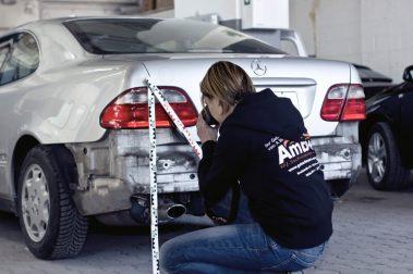 Kfz-Gutachter macht Nahaufnahme von einem Schaden am Heck eines Mercedes.