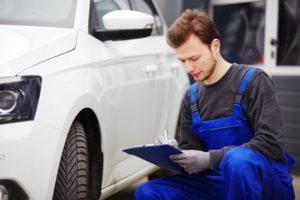 Kfz-Gutachter hakt eine Checkliste vor einem Auto ab.