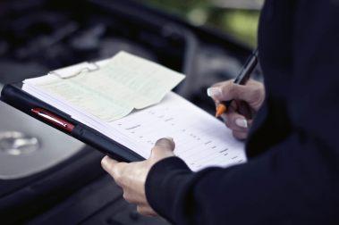 Kfz-Gutachter überprüft eine Checkliste bei der Begutachtung eines Autos.