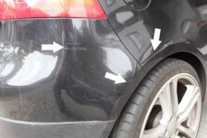Lackschaden an einem Schwarzen Auto von hinten mit weißen Pfeilen markiert.