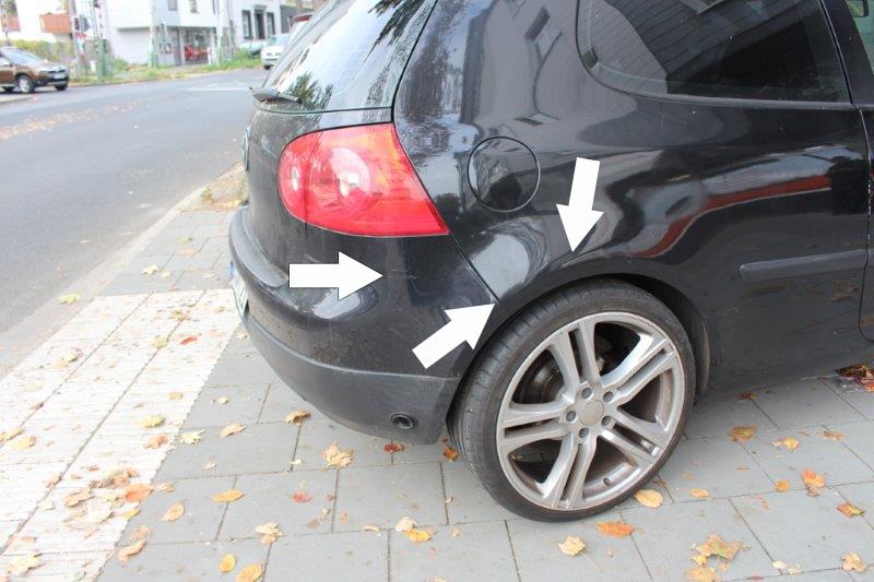 Lackschäden an einem schwarzen Auto mit weissen Pfeilen markiert.