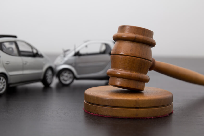 Gerichtshammer steht auf einem Tisch im Hintergrund sind 2 graue Autos.