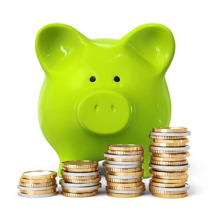 Grünes Sparschwein steht hinter einem Stapel von Münzen
