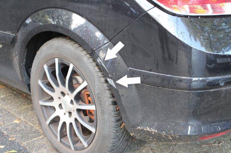 Lackkratzer an einem schwarzen Auto mit 2 weißen Pfeilen markiert.