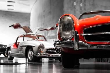 Ein roter und ein weißer Oldtimer stehen in einer Ausstellungshalle.