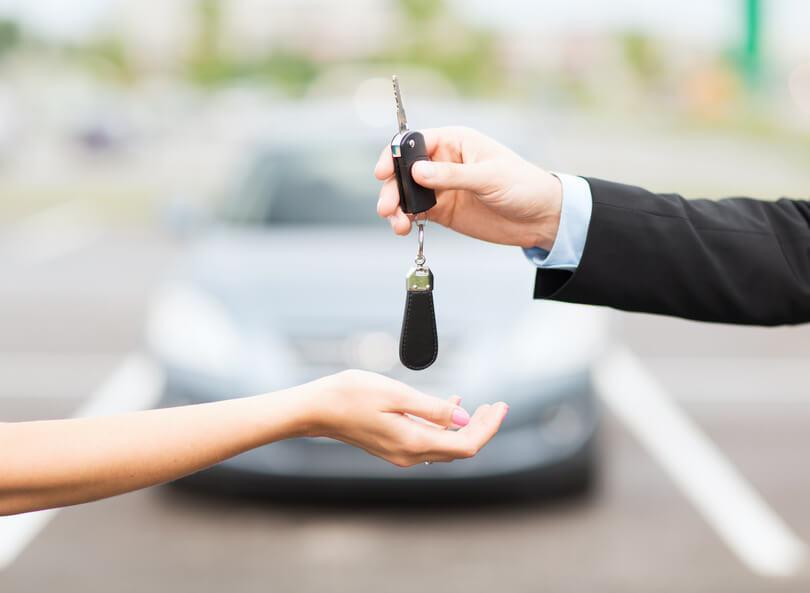 Man übergibt einen Autoschlüssel an eine Frau.