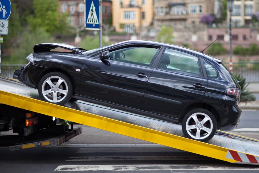 Schwarzes Unfallauto wird auf Abschlepplaster aufgeladen.