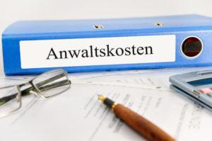 Brille, Stift, Taschenrechner und Kostenkalkulation für einen Anwalt liegen auf einem Tisch.