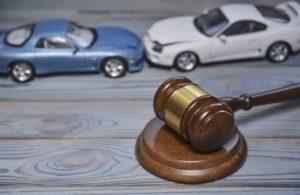 Hammer eines Richters liegt mit 2 kleinen, sich rammenden Autos auf einem Tisch.