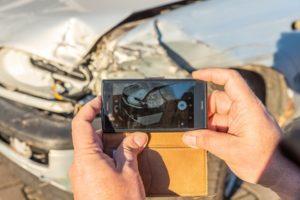Kfz-Gutachter macht ein Schadensfoto von einem kaputten Auto.