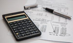 Taschenrechner, Stift und Kalkulation liegen auf einem Tisch.