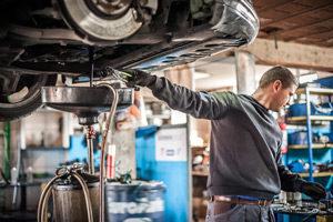 Mechaniker an Hebebühne mit Auto