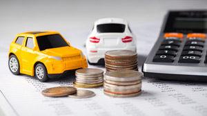 Leasingfahrzeugmodelle auf Tisch mit Geld und Taschenrechner