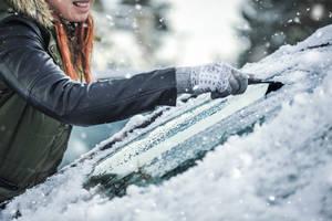 Frau beim Schneekratzen am Autor