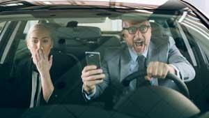 Paar im Auto mit Handy schreit auf, weil sie gerade einen Unfall verursachen.